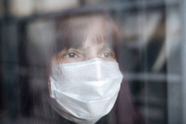 Portrait of senior women wearing a mask at home, looking out of the window - EYAF00997