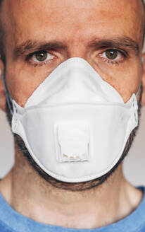 Portrait of man wearing respirator mask - JCMF00493