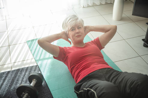 Senior woman doing sit ups at home - FRF00908