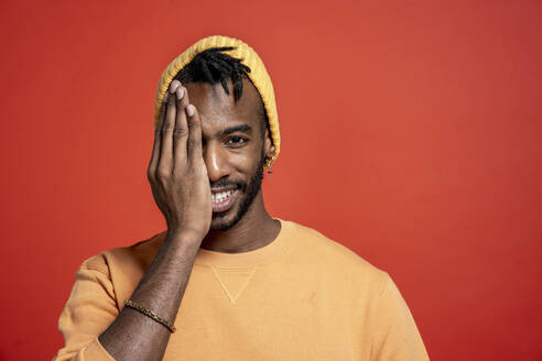 Portrait of stylish young man covering one eye in front of orange wall - VPIF02200