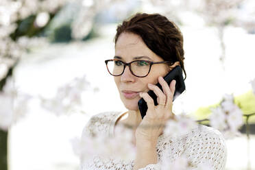 Portrait of mature woman on the phone at springtime - FLLF00442