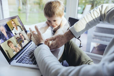 Little boy interrupting father's video conference at home - MFF05164