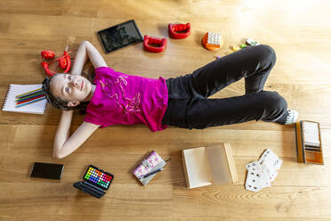 Girl lying on floor, with eyes closed, surrounded by play equipment - SARF04497