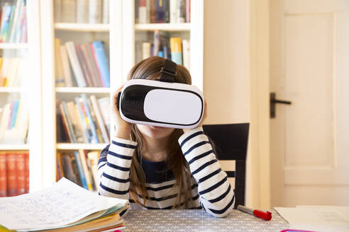 Girl sitting at table at home using virtual reality glasses - LVF08706