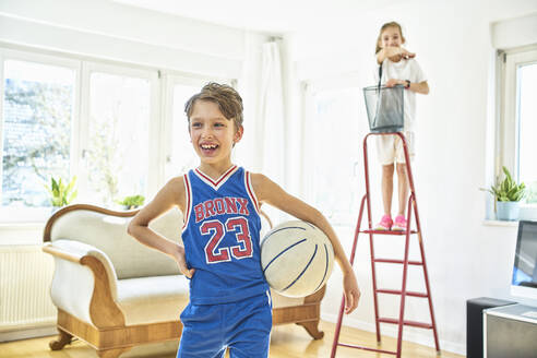 Happy boy and girl playing basketball in living room - DIKF00395