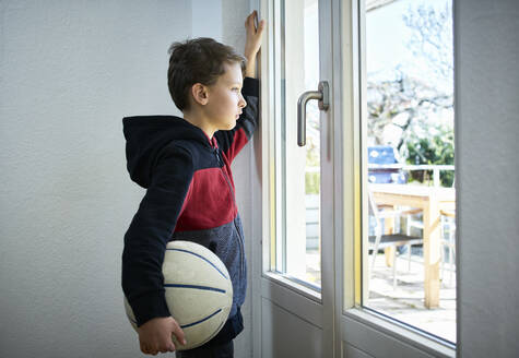 Sad boy with basketball looking out of window - DIKF00404