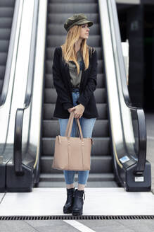 Portrait of blond young woman with bag standing in front on an escalator - JSRF00957