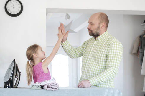 Father and daughter high fiving after ironing at home - VYF00106