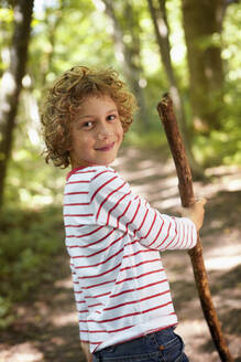 Portrait of boy with wood stick walking in forest - AUF00209