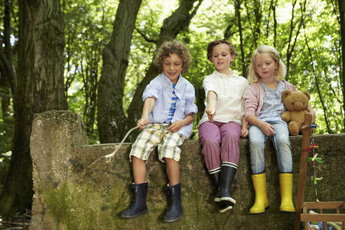 Children sitting on stone wall in forest - AUF00221