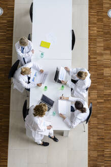 Female doctors reading papers in a meeting in conference room - BMOF00371