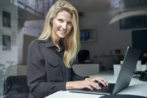 Portrait of smiling blond woman using laptop behind windowpane in office - PNEF02499