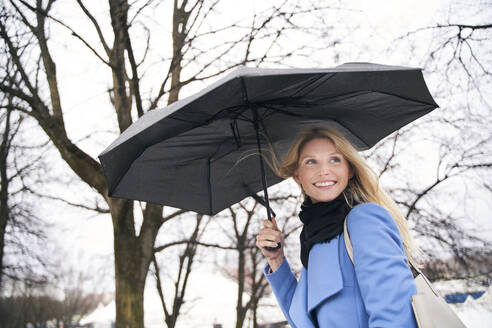 Smiling blond woman holding umbrella in storm - PNEF02505