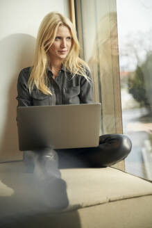 Blond woman sitting at the window using laptop - PNEF02511