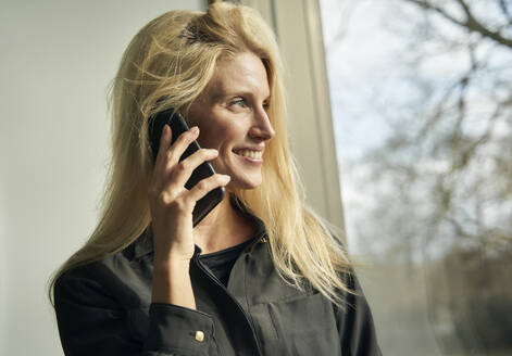 Portrait of smiling blond woman on the phone looking out of window - PNEF02514