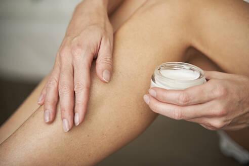 Close-up of woman applying skin cream on her leg - PNEF02535