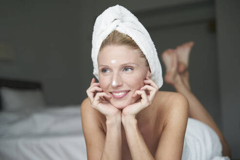 Portrait of beautiful woman with head wrapped in a towel lying on bed - PNEF02562