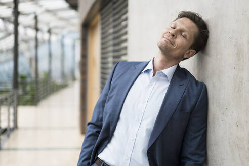 Businessman relaxing with eyes closed, leaning on wall - JOSEF00139