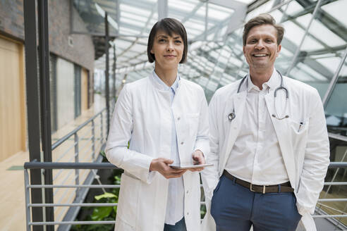 Two doctors standing in atrium, holding digital tablet - JOSEF00202