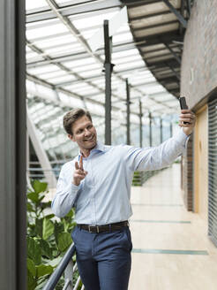 Businessman in green atrium, taking smartphone selfie, making victory sign - JOSEF00220