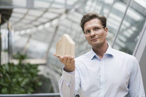 Architect holding wooden house modell, standing in sustainble building - JOSEF00238