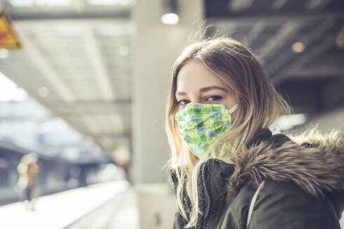 Portrait of young woman wearing mask at station platform - BFRF02207
