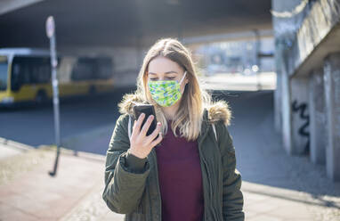 Young woman with smartphone wearing mask in the city - BFRF02213