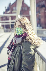 Portrait of young woman wearing mask on a bridge in the city - BFRF02216