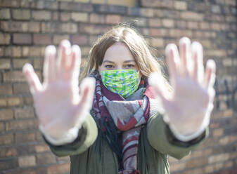 Portrait of young woman wearing mask raising her hands - BFRF02219