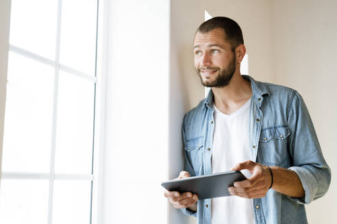 Young smiling man at home holding his tablet and looking outside of his window - SBOF02147