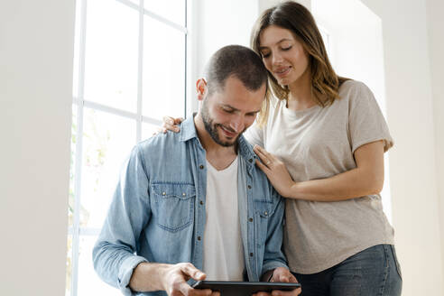 Smiling couple at home in front of window looking at tablet together - SBOF02159