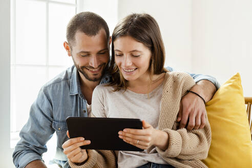 Happy couple at home in their living room in front of window looking at tablet together - SBOF02180