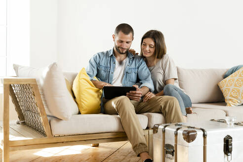 Smiling couple at home in modern living room sitting on couch while looking at tablet together - SBOF02189