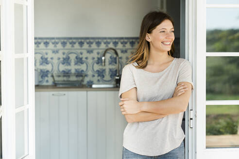 Attractive young woman standing in the door at home and smiling - SBOF02210