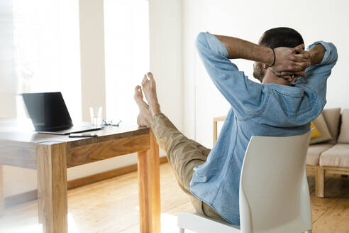 Young man at home working in home office and relaxing in modern living room with his feet on the table - SBOF02216