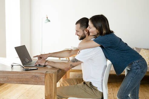 Smiling couple working at laptop from home in home office in modern living room - SBOF02222
