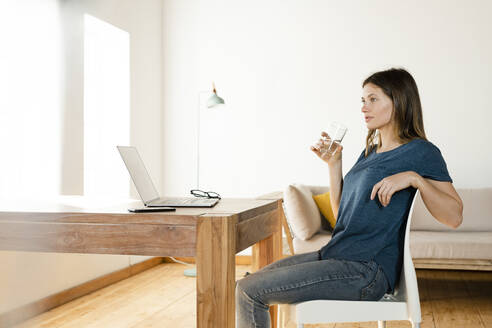 Young woman drinking a galss of water and having a break from working at laptop in home office - SBOF02225