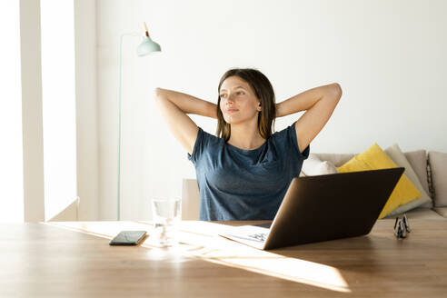 Content young woman at home having a break from working at laptop in home office - SBOF02228