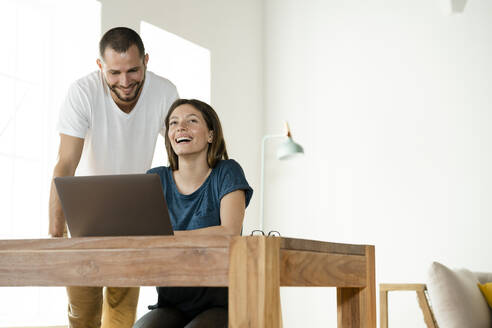 Happy couple working at laptop from home in home office in modern living room - SBOF02234
