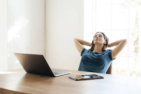 Young woman with laptop in home office having a break - SBOF02255