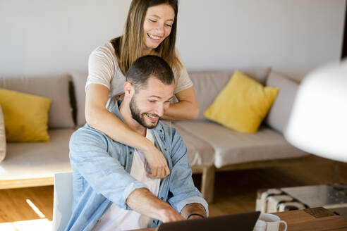 Happy young couple using laptop at home - SBOF02264