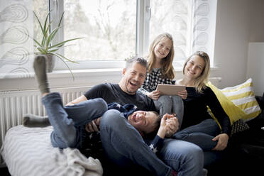 Portrait of happy family having fun on couch at home - HMEF00844