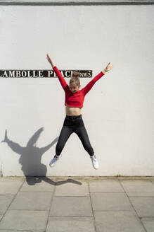 Exuberant young woman jumping in front of a wall - FBAF01357