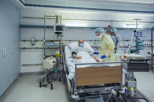 Doctors caring for patient in emergency care unit of a hospital taking blood sample - MFF05315