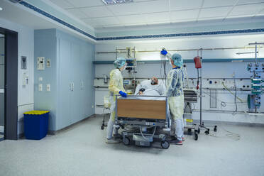 Doctors caring for patient in emergency care unit of a hospital with respiratory equipment - MFF05327