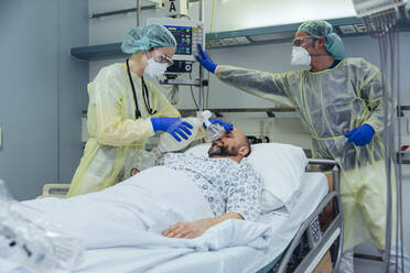 Doctors with bag valve mask caring for patient in emergency care unit of a hospital - MFF05330