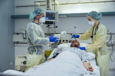Doctors caring for patient in emergency care unit of a hospital changing breathing from oxygen mask to bag valve mask - MFF05339