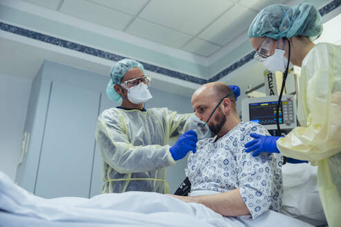 Doctors giving artificial respiration to patient in emergency care unit of a hospital - MFF05342