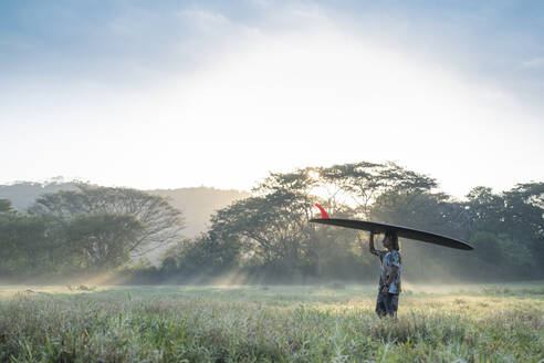 Young man carrying his surfboard on head at sunrise, Costa Rica - AMUF00030