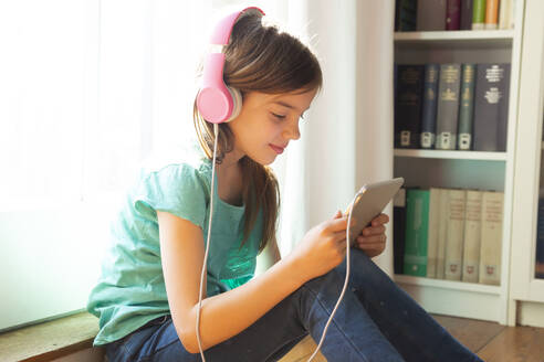 Smiling girl sitting on the floor at home using headphones and digital tablet - LVF08730